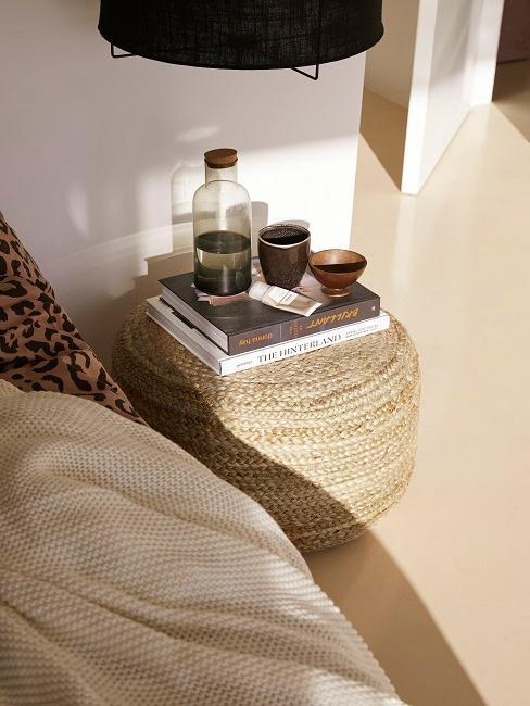 Pouf en jute servant d'espace de rangement, posé à côté du lit