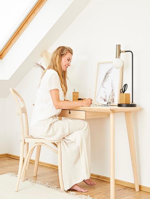 Frau an einem Schreibtisch aus Holz, darauf ein schlichtes Bild im Holzrahmen als Deko