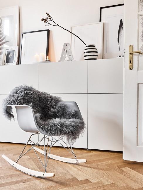 Stuhl zum Schaukeln mit grauem Lammfellimitat vor einem hellen Sideboard mit viel Deko