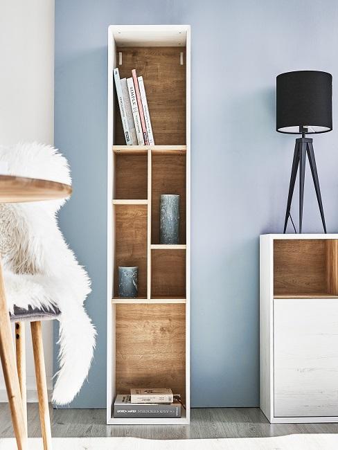 Tisch mit Stuhl aus Holz, ein schmales, clean eingerichtetes Regal aus hellem Holz und ein Sideboard mit Stehlampee