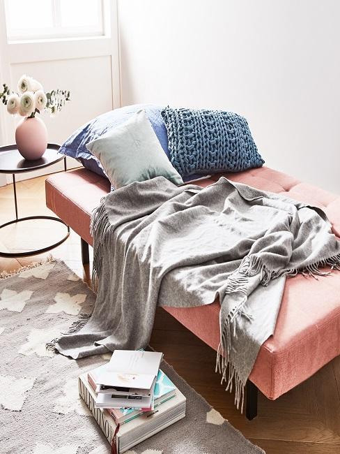 Gästebett in Rosa und gemütlichen Kissen und grauer Decke