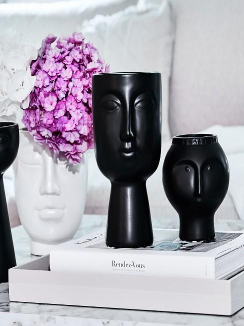 White and black vase with face on table