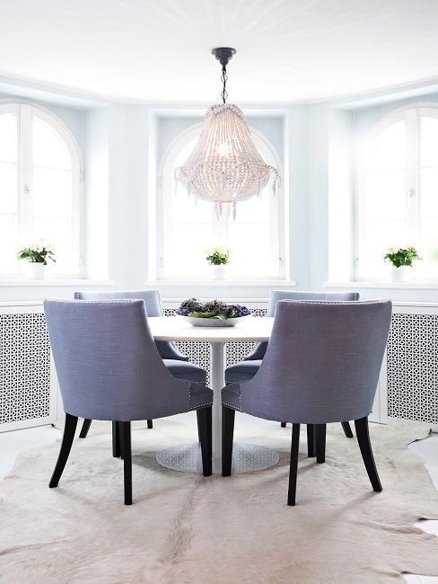 Esszimmer im Erker mit einem runden Tisch und vier grauen Stühlen aus Samt und mit schwarzen Beinen.