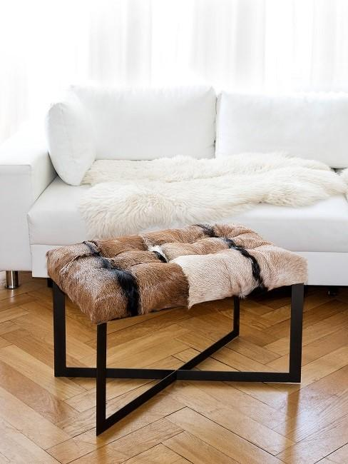 Fellhocker in braun vor weißem Sofa