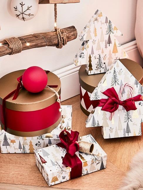 Mehrere verpackte Geschenke in Geschenkpapier und Boxen auf dem Boden vor einer Holzleiter mit Weihnachtskugel und Lichterkette