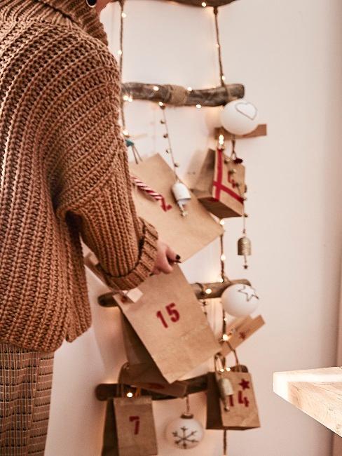 Eine Frau befestigt den Adventskalender us Papiertüten an einer hängenden Holzleiter mit Lichterkette und Weihnachtskugeln zur Weihnachtsdeko