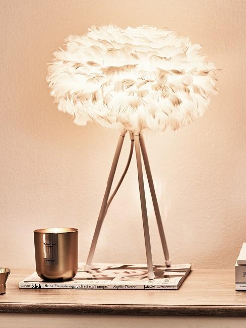 Leuchtende Wolkenlampe auf Tisch mit Buch und Deko