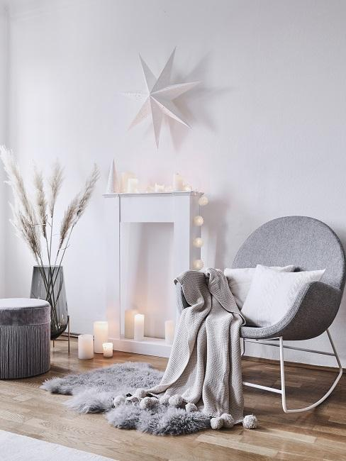 Weiße Kamin-Attrappe dekoriert mit Kerzen und Lichterkette neben grauem Sessel mit Kissen und Decke