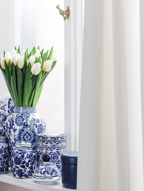 Fensterbrett mit vielen Vasen und Porzellan als Deko in Blau-Weiß, dazu eine weiße Gardine