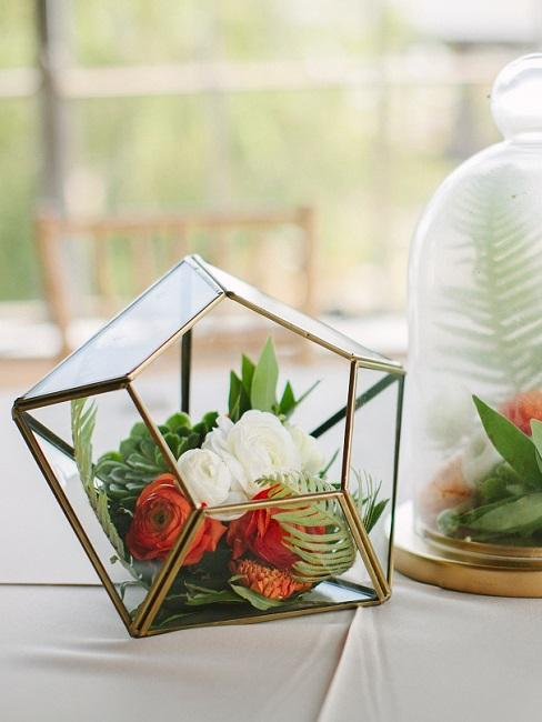 Two different variants of flower decoration in a glass lying on a table