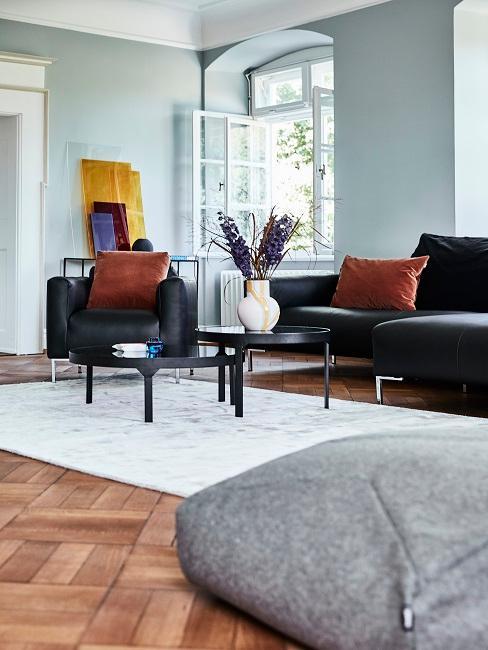 Wohnzimmer mit schwarzer Ledercouch im nordischen Chic