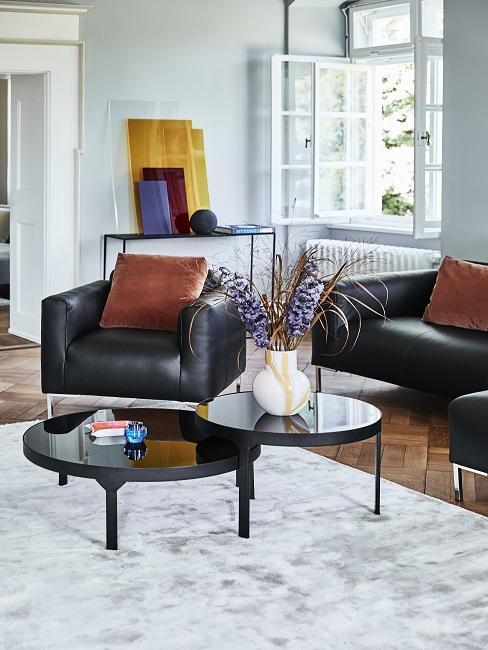 Richtig lüften Wohnzimmer mit schwarzen Ledersesseln, braunen Kissen und schwarzem Couchtisch
