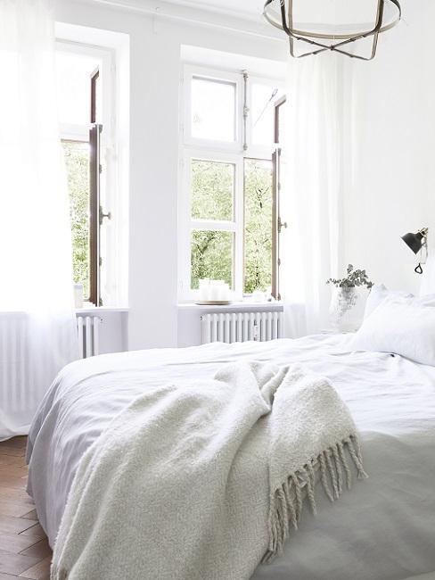 Helles Schlafzimmer mit zwei geöffneten Fenstern