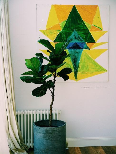 Eine kleine Heizung mit großer Pflanze davor, sowie einem Vorhang, darüber ein modernes Wandbild in Gelb-Grün