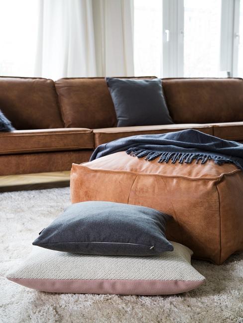 Lederarten brauner Pouf aus Glattleder auf dem Bodem neben Kissen und Sofa