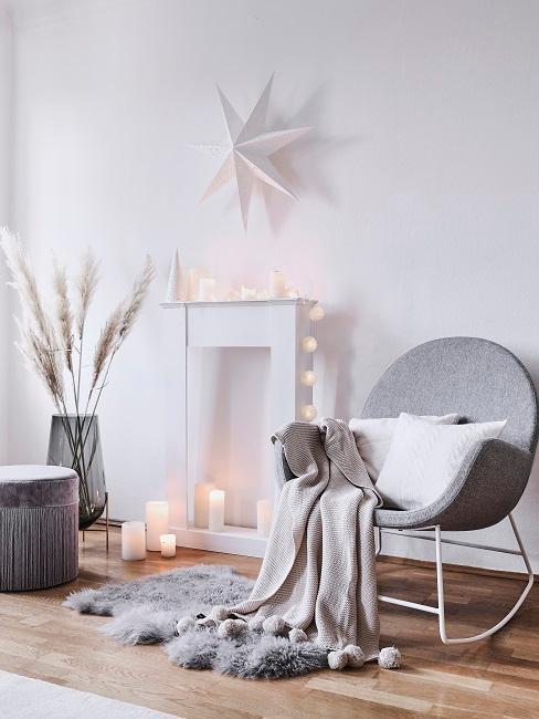 Ecke im Wohnzimmer mit einem Sessel, Pouf und Deko-Kaminkonsole, ein Stern als Wanddeko darüber
