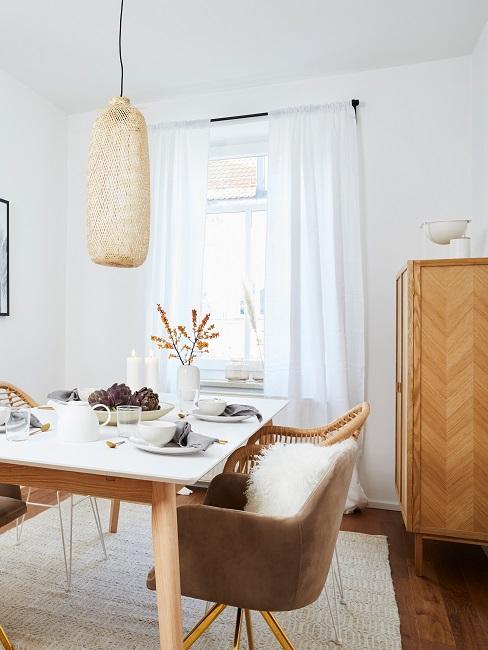 Wohnzimmer mit Essbereich mit Möbeln aus hellem Holz und einer Rattanlampe im skandinavischen Stil