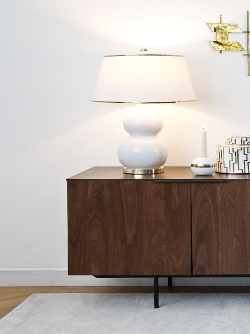 Große weiße Lampe mit Keramikfuß auf braunem Sideboard