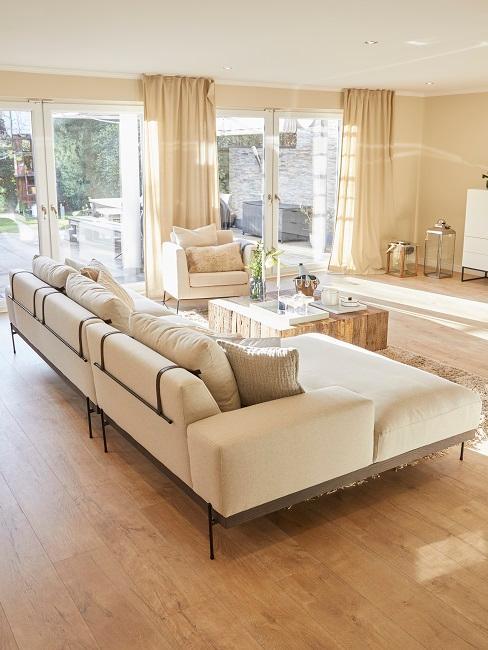 Das helle Wohnzimmer von Jana Ina Zarrella vom Wohnzimmer Eingang aus mit der Rückansicht des hellen Sofas in der Raummitte