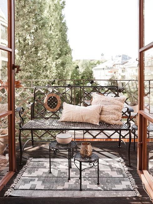 Kleiner Balkon mit Metallbank und beigen Kissen, zwei kleinen Tischen und einem Teppich, alles im orientalischen und dem Ethno Stil