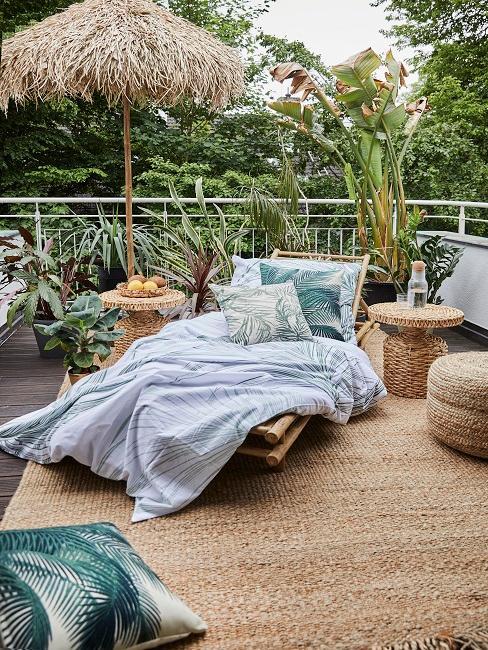 Große Terrasse mit Naturmaterialien: Einem Stroh Sonnenschirm, einer Bambus Sonnenliege und Rattanmöbeln, viele Pflanzen und Kissen dienen als Deko