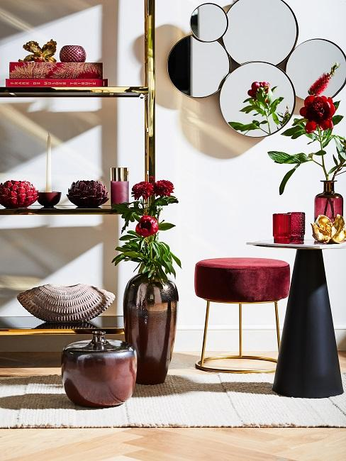 Golden metal shelf decorated with candles, bowls, books and objects next to a mirror and floor vases