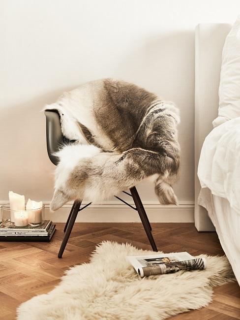 Stuhl mit Fell neben Bett