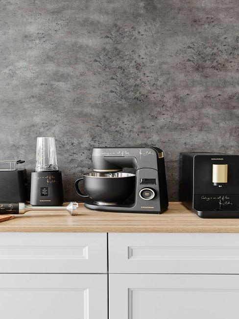 Küchenzeile mit schwarzen Küchenmaschinen vor Betonwand