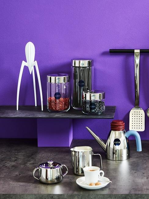 Kaffee auf dunkler Küchenzeile vor einer knall Lila Wand