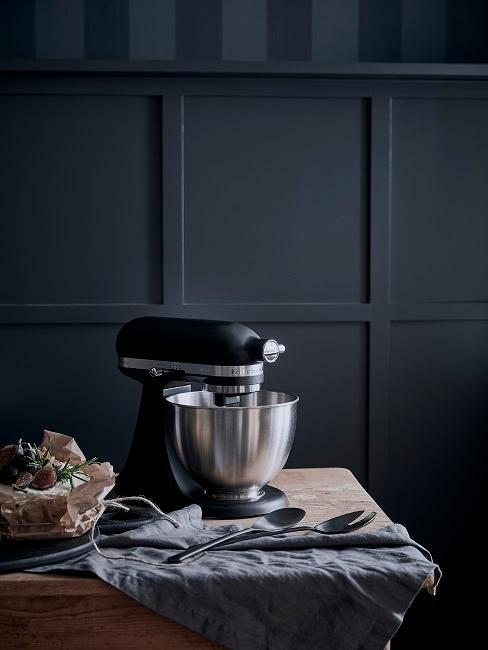 Küchengerät auf Holztisch vor schwarzer Wand