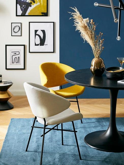 Gelber Stuhl in blauem Esszimmer mit Wandbildern und schwarzem Tisch