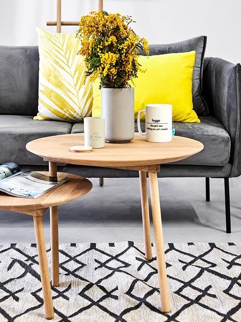 Graues Sofa mit gelben Kissen hinter Beistelltischen mit gelben Blumen in grauer Vase