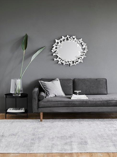 Graue Wohnzimmerwand mit Sofa, silbernen Spiegel und Pflanze