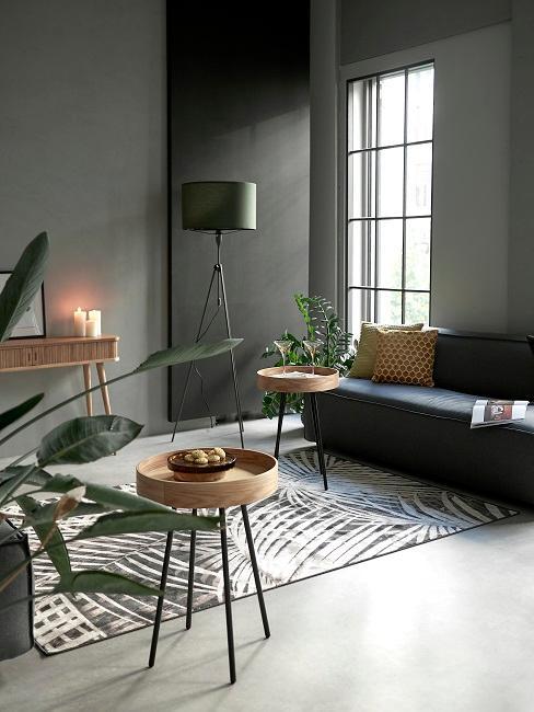 Graue Wandfarbe im Wohnzimmer mit schwarzen Sofa und Pflanzen