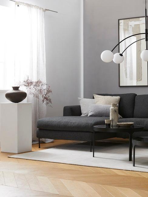 Hellgraue Wandfarbe hinter schwarzem Sofa