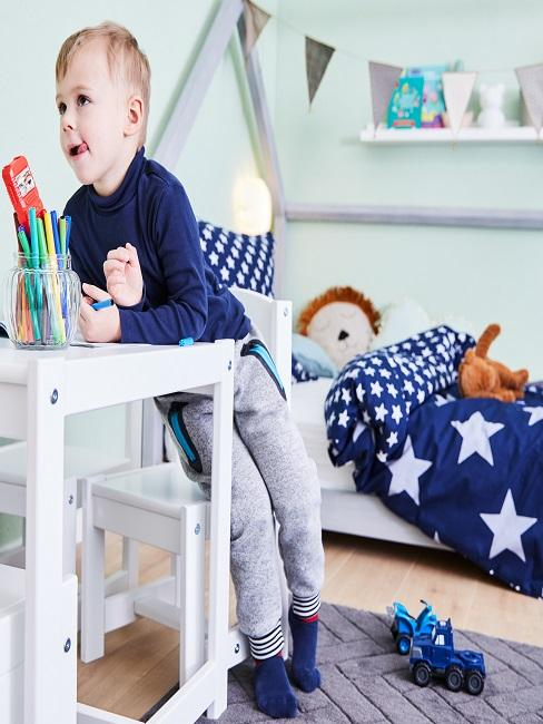 Kind im Kinderzimmer am Maltisch