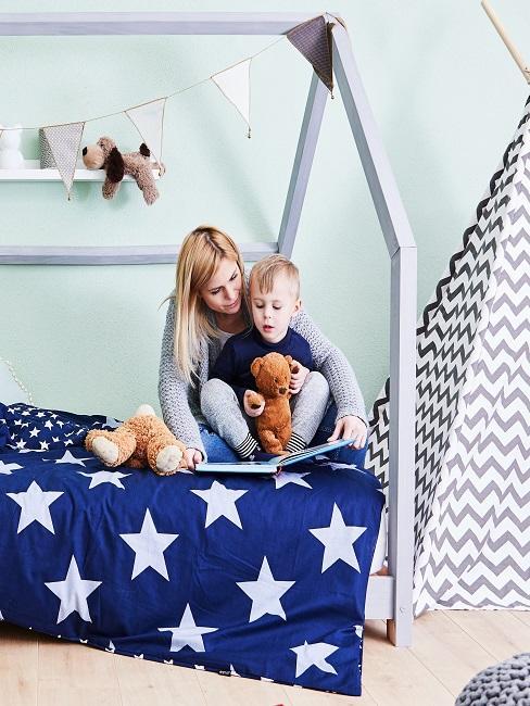 Kind mit Mama am Buch vorlesen auf dem Bett mit Sternebettwäsche