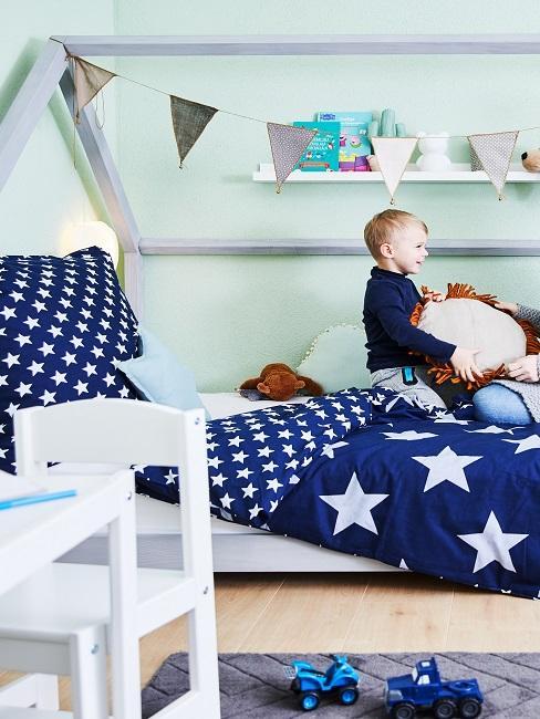 Kind im Bett mit Sternenbettwäsche am Spielen