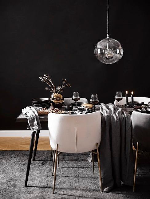 Schwarze Wandfarbe im Esszimmer mit weißen Stühlen und Pendelleuchte in Silber