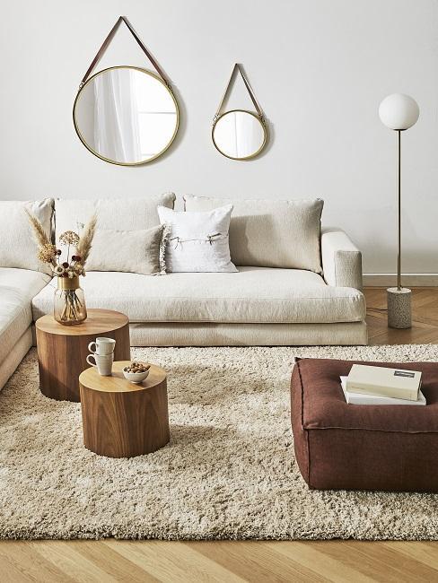 Helle Wandfarbe im Wohnzimmer mit weißer Wand, runden Spiegeln, cremefarbenen Sofa und Teppich und brauner Pouf