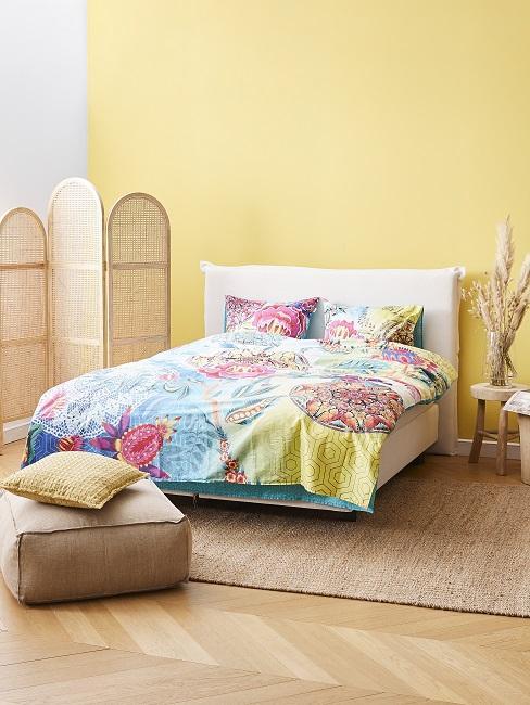 Helle Wandfarbe in Gelb im Schlafzimmer mit bunter BEttwäsche und Accessoires aus Naturmaterialien
