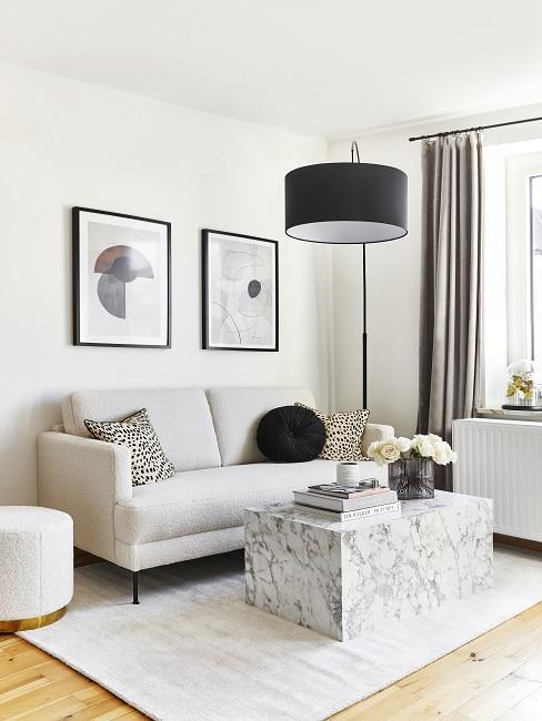 Wohnzimmer in erster eigener Wohnung mit grauem Sofa, Marmortisch, schwarzer Stehlampe und Deko