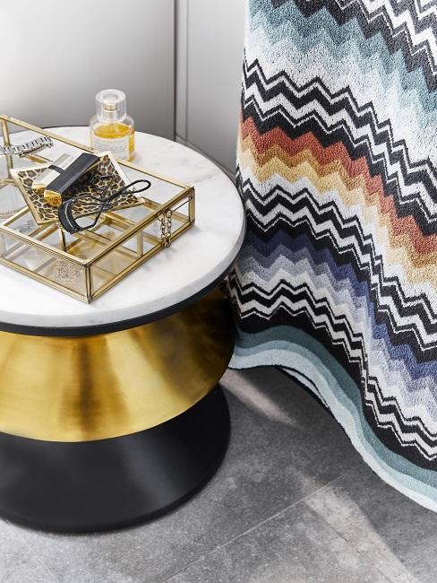 Gold-schwarzer Beistelltisch mit Schmückkästchen neben buntem Handtuch