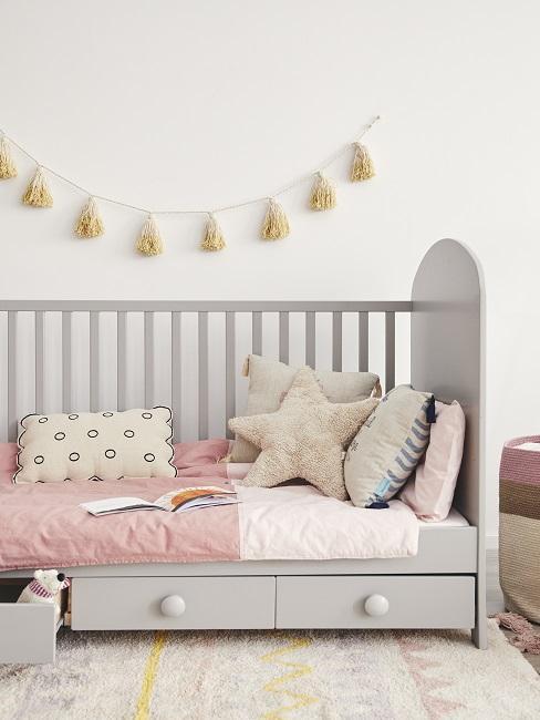 Graues Kinderbett mit bunten Dekokissen und Girlande