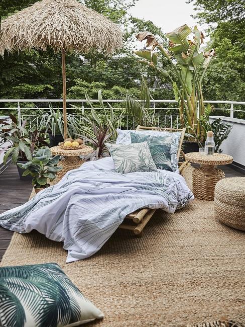 Balkon mit Sonnenliege, Kissen, Teppich und Tischen aus Jute
