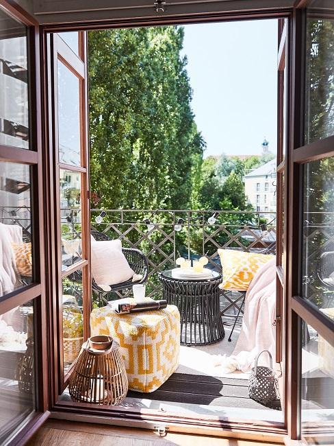 Kleinen Balkon gestalten mit schwarzen Stühlen, Tisch, gelben Kissen und Sitzpouf