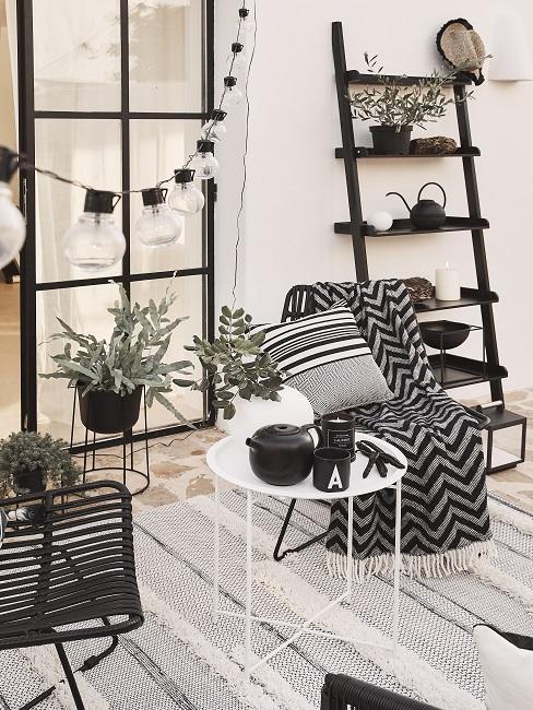 Balkon gestalten in Schwarz-Weiß mit Lichterkette, Wohntextilien, Pflanzen und Dekoleiter