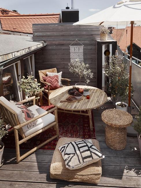 Zwei Sessel, Tisch, Hocker und Jutekissen auf Balkon mit Ethno-Kissen