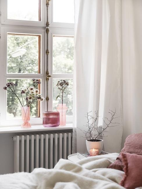 Flower arrangements in three pink vases on windowsill