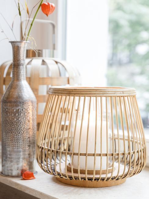 Velas, jarrón metálico al lado de la ventana con luz natural